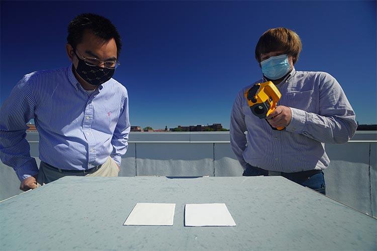 El profesor Xiulin Ruan (izquierda) y el estudiante de doctorado Joseph People (derecha) estudian la pintura de enfriamiento radiativo Purdue y las muestras de pintura comercial colocadas una al lado de la otra