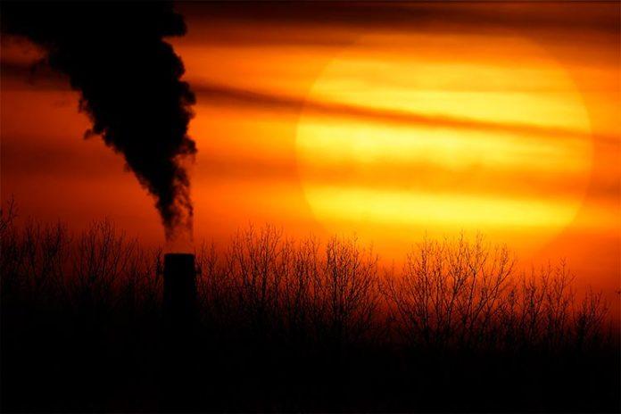 En esta fotografía de archivo del 1 de febrero de 2021, las emisiones de una central eléctrica de carbón se recortan contra el sol poniente en Independence, Missouri. Un informe de las Naciones Unidas publicado el jueves 18 de febrero de 2021 drhits que los humanos están convirtiendo a la Tierra en un planeta roto y cada vez más inhabitable debido al cambio climático, la pérdida de biodiversidad y la contaminación