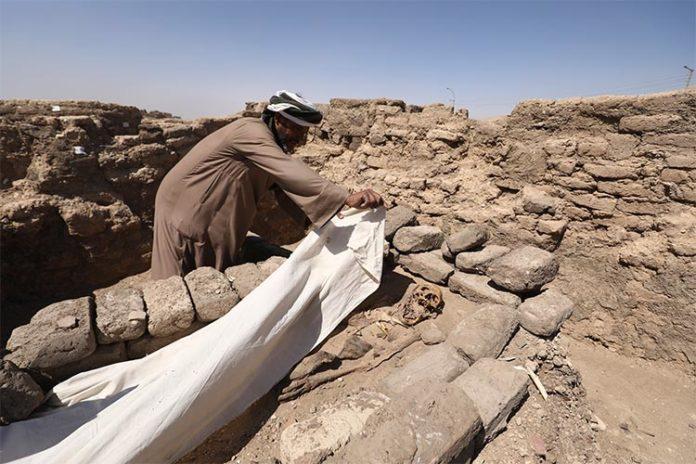 Un hombre cubre un esqueleto en una ciudad perdida de 3.000 años de antigüedad en la provincia de Luxor, Egipto, el sábado 10 de abril de 2021