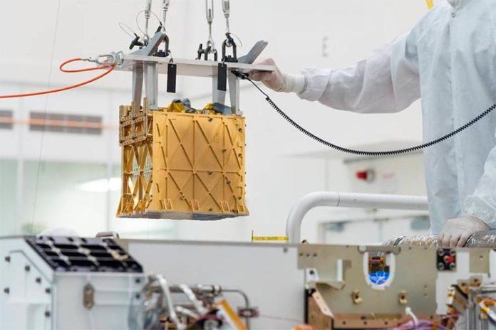 Técnicos del Laboratorio de Propulsión a Chorro de la NASA bajan el instrumento del Experimento de Utilización de Recursos In-Situ de Oxígeno de Marte (MOXIE) al vientre del rover Perseverance
