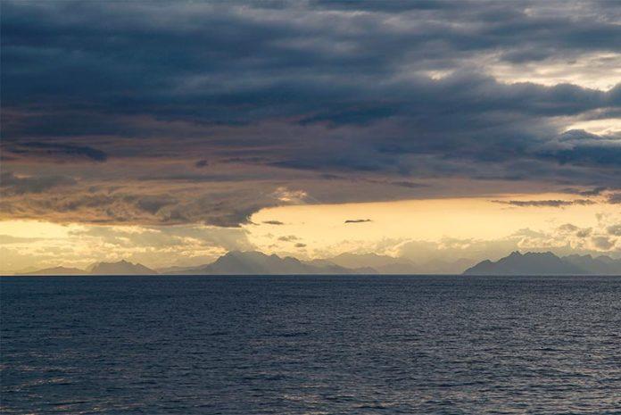Nubes cargadas y la costa sur de Alaska enmarcan el Golfo de Alaska durante un crucero científico en el verano de 2017